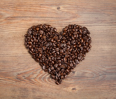 Overhead view of coffee beans arranged in a heart shape on a brown wooden background with copy space.